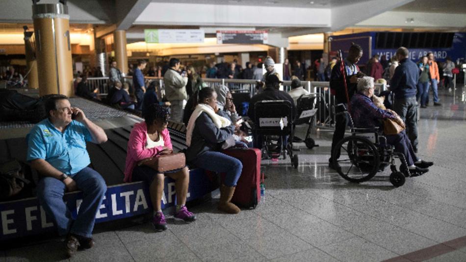 Flugpassagiere sitzen am in Atlanta vor dem Flughafengebäude des Hartfield-Jackson Flughafens an einem Generator und laden ihre Mobiltelefone auf. Nur eine Woche vor Weihnachten hat ein totaler Stromausfall den verkehrsreichsten Airport der Welt lahmgelegt. Das wiederum löste ein Chaos im Flugverkehr aus.