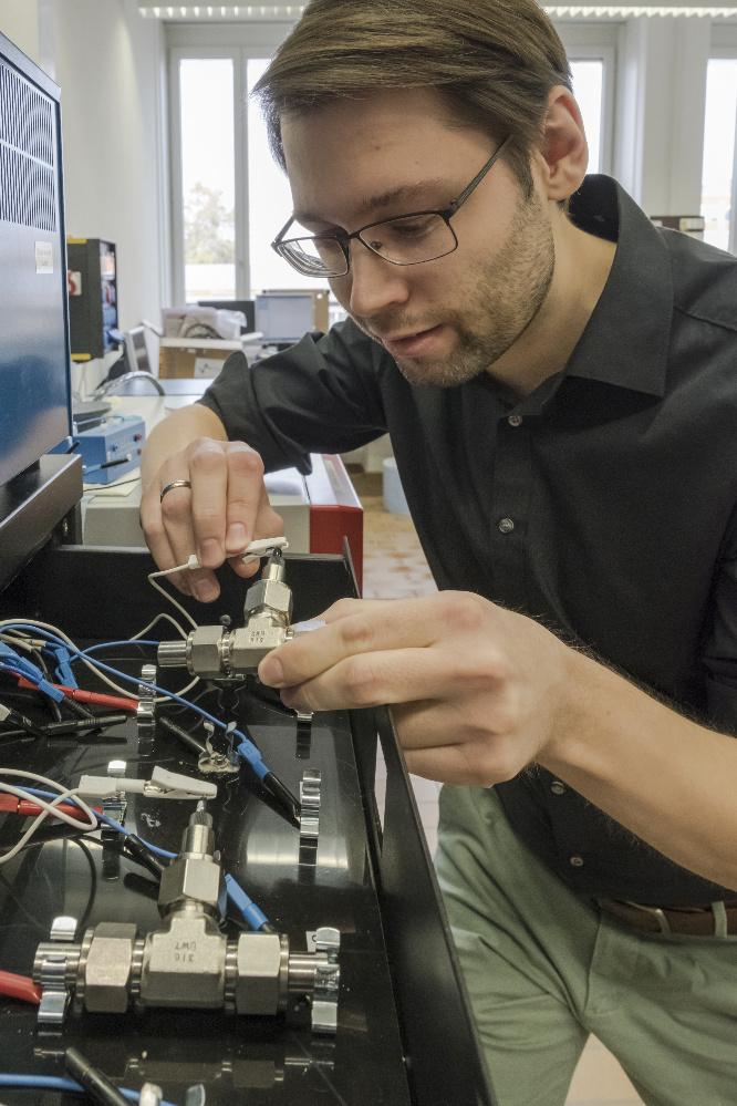 Empa-Forscher schließt eine Testzelle mit der konzentrierten Salzlösung ans Ladegerät an.