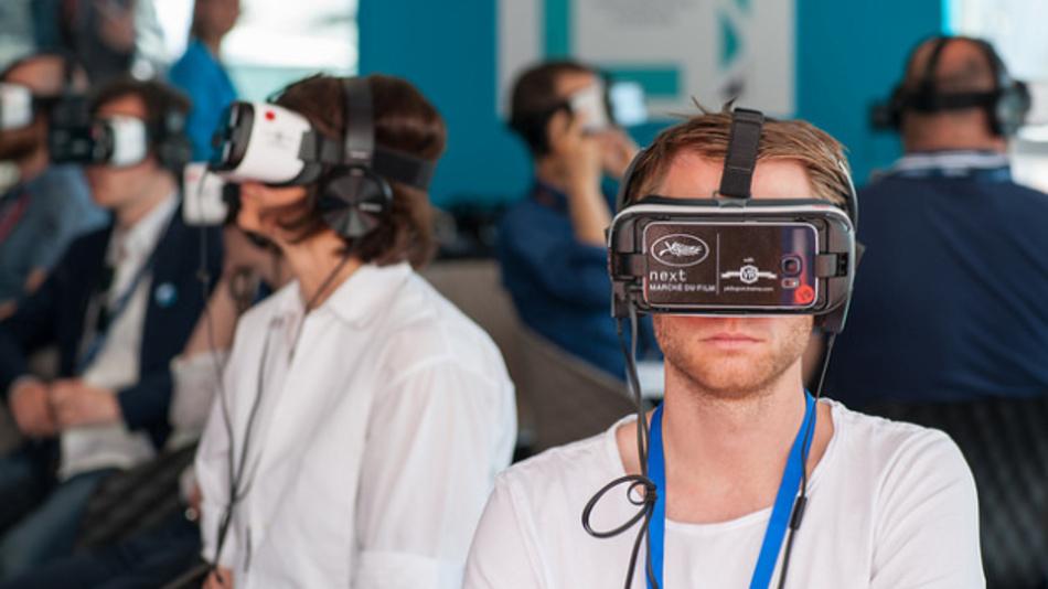 Ein Besucher des Marché du Film-Festivals in Cannes probiert ein VR-Headset aus.