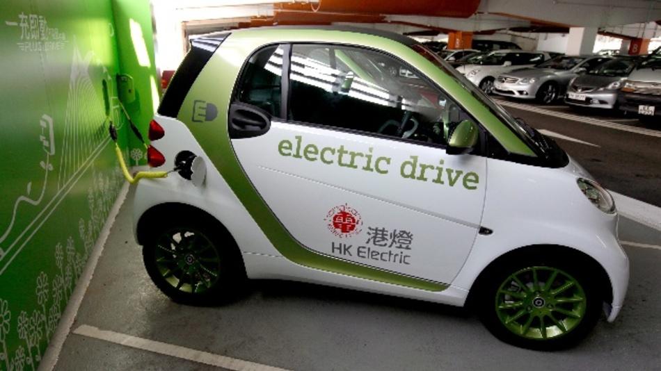 Ein Mercedes-Benz Smart Fortwo Elektroauto tankt an einer öffentlichen Ladestation in Hongkong auf.