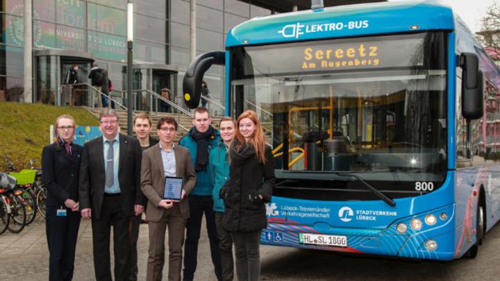Bettina Lange, Jens Lottmann, Jacob Stahl, Prof. Thomas Franke, Daniel Herrmann, Markus Gödker und Vivien Moll vor einem E-Bus in Lübeck.