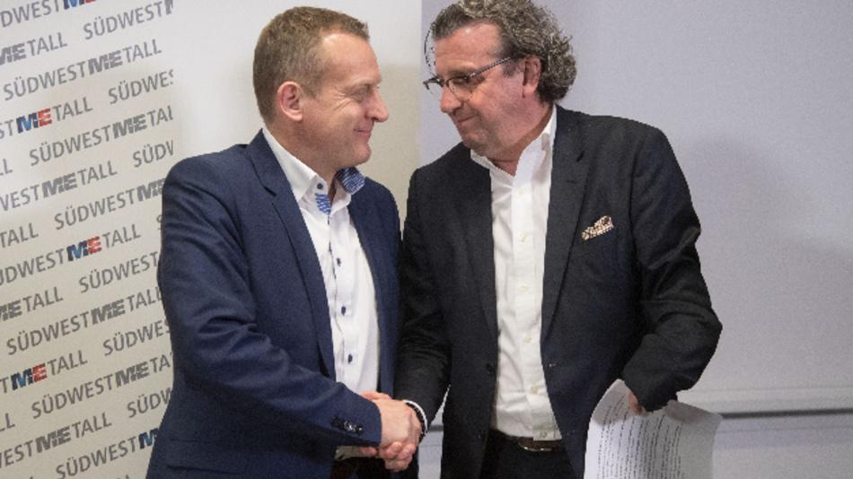 Stefan Wolf (r.), der Vorsitzende der Arbeitgebervereinigung Südwestmetall und Roman Zitzelsberger, der Bezirksleiter der IG Metall Baden-Württemberg, geben sich  zum Abschluss der Tarifverhandlungen die Hand.