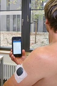 Der Glukosesensor wird am Oberarm unter die Haut implantiert, die Werte werden an das Smartphone geschickt und über eine App ausgelesen.