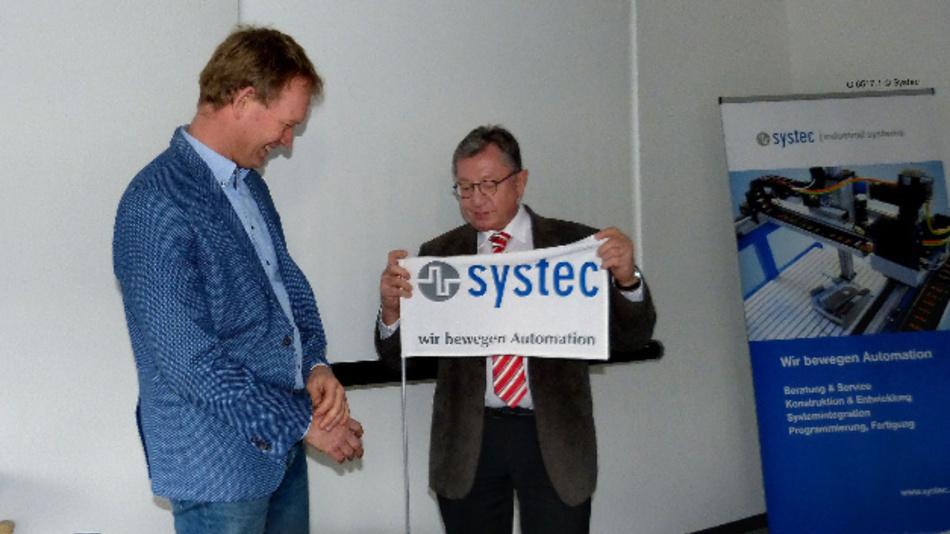 Niederlassungsleiter Jan Leideman (links) hält jetzt die Fahne der Systec GmbH in Münster hoch. Der scheidende Geschäftsführer Tilmann Wolter übergab ihm die Leitung des Unternehmensstandorts im Rahmen einer kleinen Zeremonie.