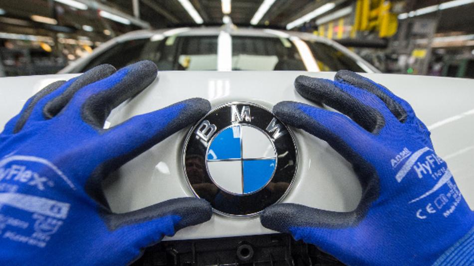 Ein Mitarbeiter montiert im BMW Werk ein Emblem auf den Kofferraumdeckel – durch die Blockchain wird künftig bekannt, in welchem Werk.