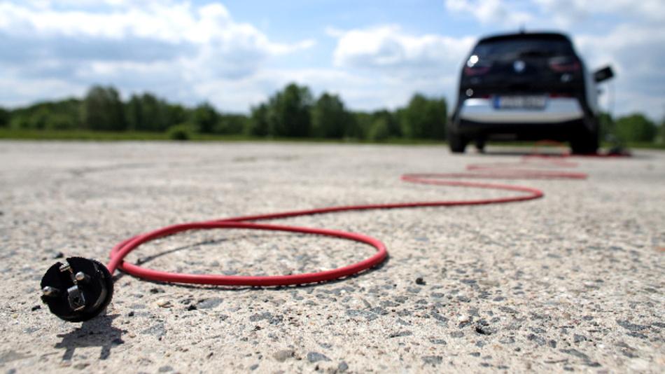 Ein rotes Stromkabel liegt hinter einem elektrisch angetriebenen BMW i3: E-Autos entwickeln sich zum Hoffungsträger der Automobilindustrie