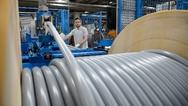 Ein Mitarbeiter des Kabelherstellers Lapp kontrolliert das Aufrollen eines Kabels.
