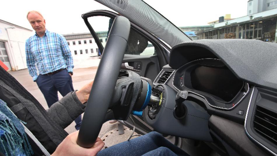 Bernhard Schick vom Forschungsbereich Fahrerassistenzsysteme der Hochschule Kempten steht an einem mit Messgeräten ausgestatteten Auto.