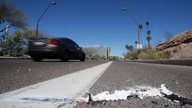 Ein Auto fährt an einem Unfallort vorbei. Erstmals ist ein Mensch bei einem Unfall mit einem selbstfahrenden Autos ums Leben gekommen. Ein Roboterwagen des Fahrdienst-Vermittlers Uber erfasste am 19.03.2018 eine Frau, die die Fahrbahn überquerte.