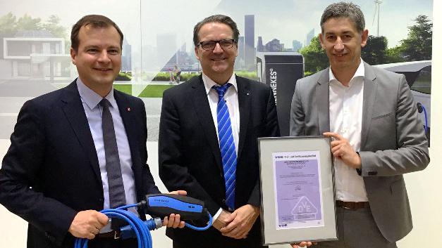 Sven Öhrke (Mitte) übergibt auf der Light & Building 2018 das VDE-Zertifikat an Christopher Mennekes (links) und Volker Lazzaro (rechts) für die Steuer- und Schutzeinrichtung (IC-CPD) zum Laden von Elektrofahrzeugen.