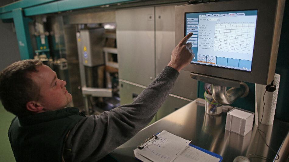 Bauer Hendrik Vedder steuert den Melkroboter im Kuhstall.