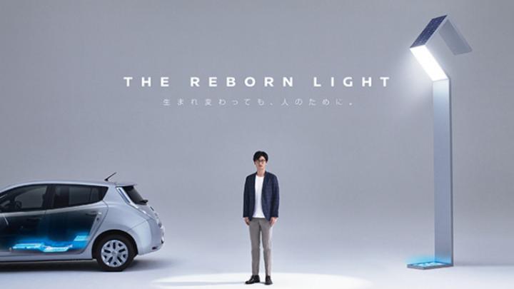 Mann steht zwischen Nissan Leaf und Straßenlaterne