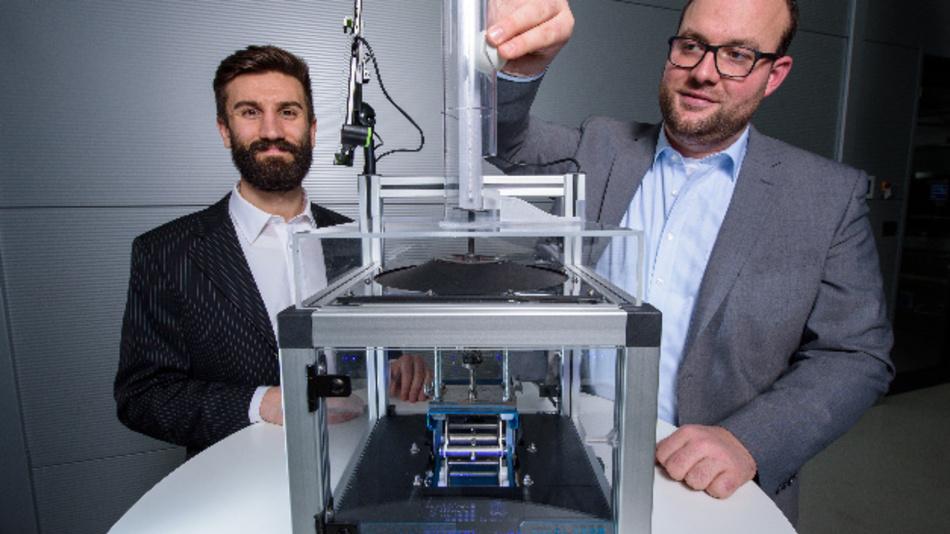 Mit dieser Apparatur zeigen die Ingenieure Paul Motzki (l.) und Philipp Linnebach (r.) die neue Technologie auf der Hannover Messe: Hierzu lassen sie einen Ball auf die Folie fallen.