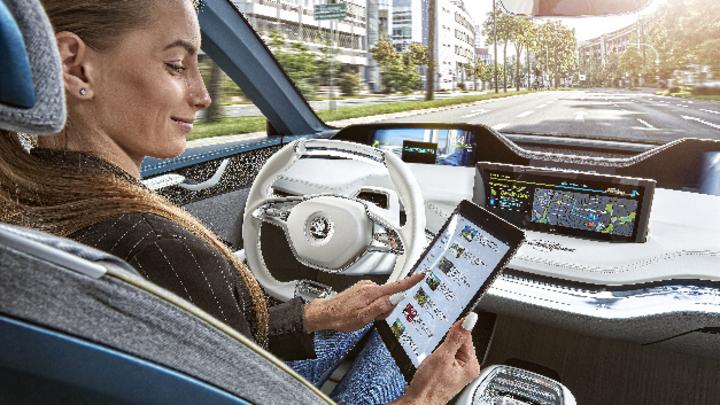 Frau in einem autonomen Auto mit Tablet in der Hand