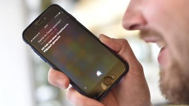 Mann nutzt Spracherkennungssoftware Siri auf seinem Smartphone