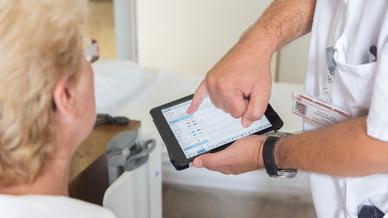 Mobile Visite: Mithilfe von Tablet-PCs können Ärzte Patienten direkt am Patientenbett besser ihre gesundheitliche Lage erklären.