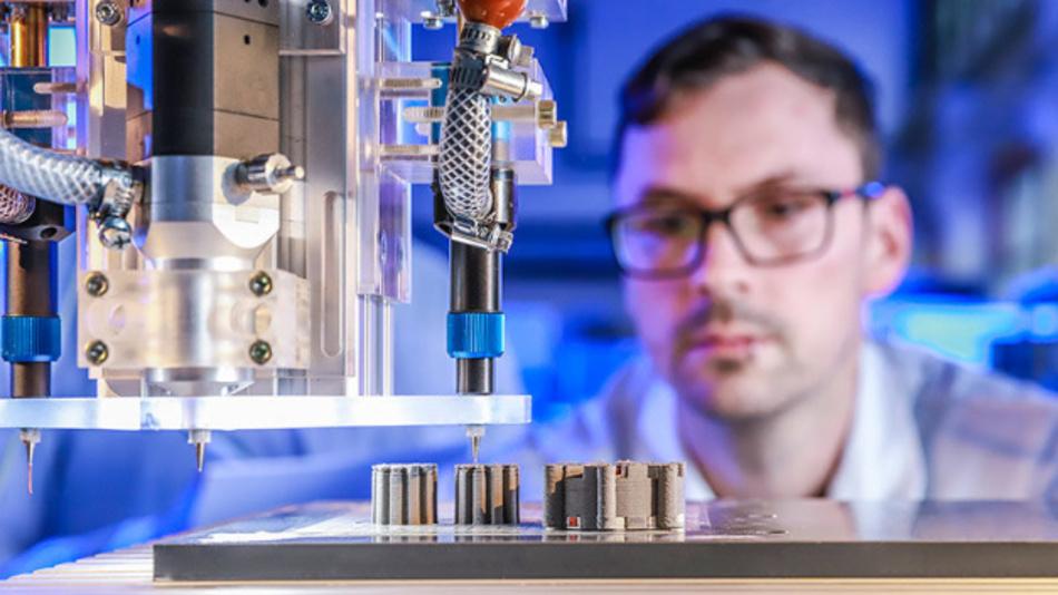 Johannes Rudolph überwacht im Labor den 3D-Multimaterialdruck einer elektrischen Maschine bei dem erstmals Kupfer, Keramik und Eisen gleichzeitig in einem Druckprozess zum Einsatz kommen. Links sind die Rotoren zu erkennen, rechts der Stator. Foto: Jacob Müller.