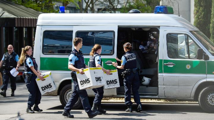 Polizisten tragen Pappkartons zu einem Polizeiauto neben einem Porsche-Gebäude.