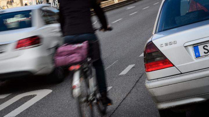Zwischen der Autofahrbahn und geparkten Wagen ist für eine Radfahrerin nur wenig Platz