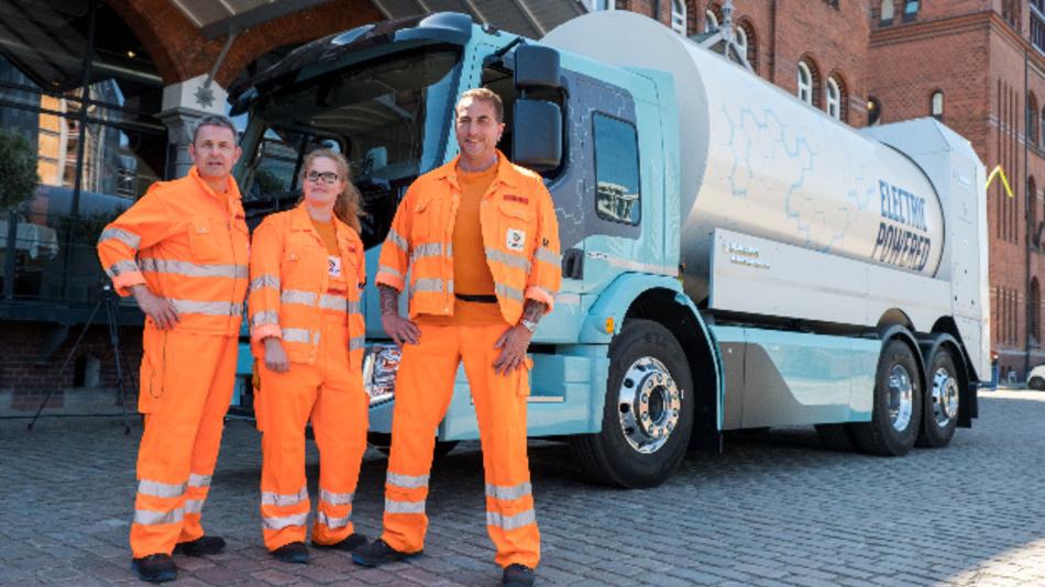 Erik Siersleben (l-r), Yvonne Möller und Horst Radek, Mitarbeiter der Stadtreinigung Hamburg, stehen vor einem elektrobetriebenen Müllwagen vom Typ Volvo FE Electric. Volvo hat das erste Müllfahrzeug mit Elektroantrieb an die Stadtreinigung übergeben.