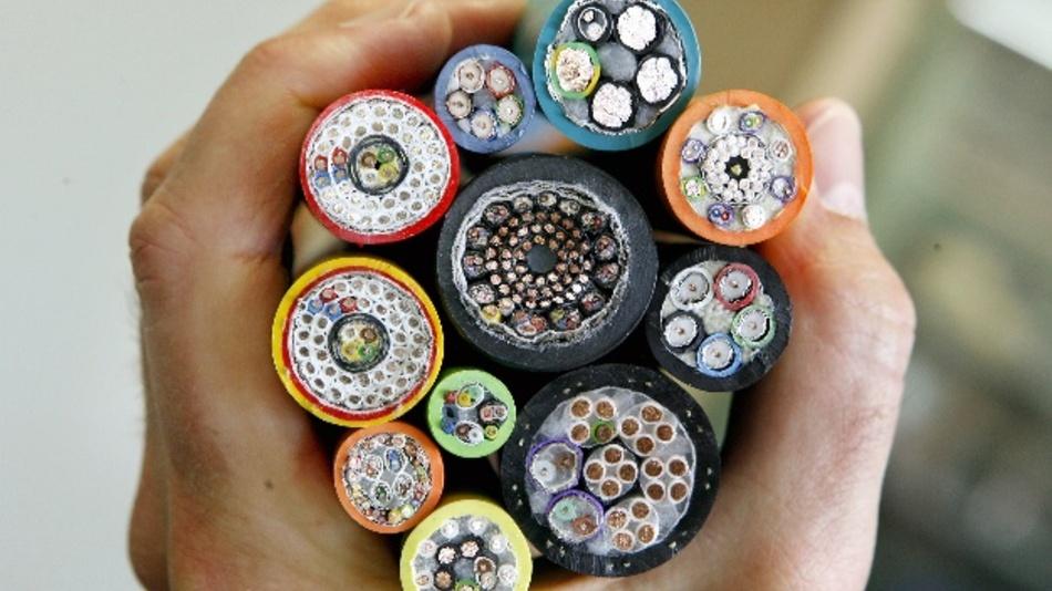 Ein Mitarbeiter des Kabel- und Bordnetzherstellers Leoni AG hält in der Produktionsstädte verschiedene Spezialkabel in der Hand.