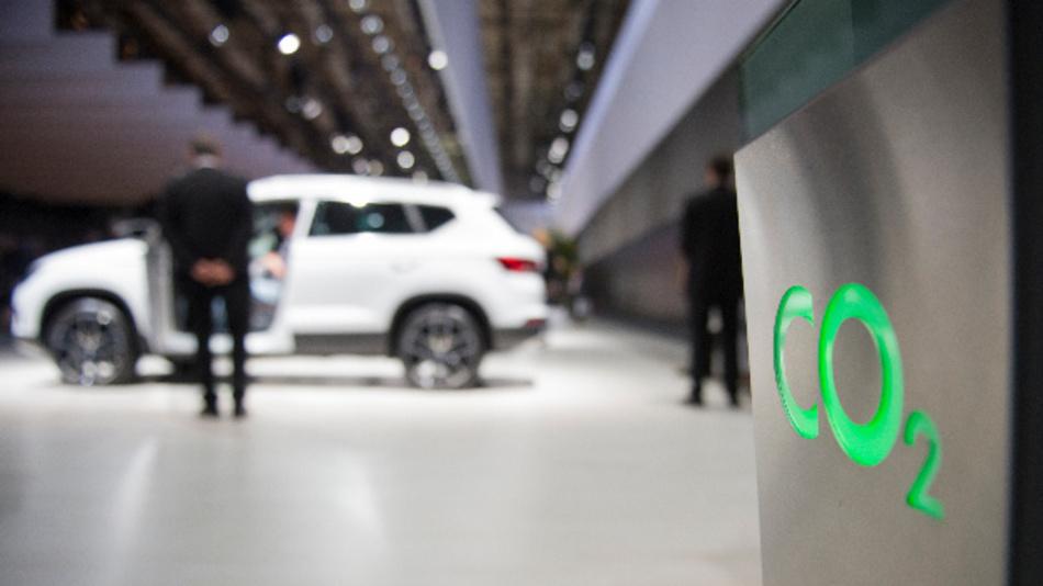 Grüner Schriftzug »CO2« an einer Stehle in der Nähe eines Seat Ateca.