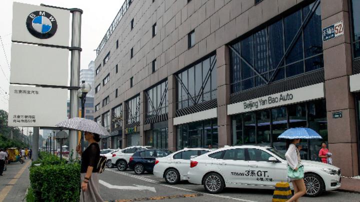 Eine Frau geht mit einem Regenschirm am Geschäft eines BMW Händlers vorbei