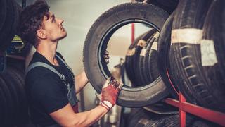 Ein Automechaniker in einer Reparaturwerkstatt wählt die richtigen Reifen für einen bestimmten Fahrzeugtyp aus.