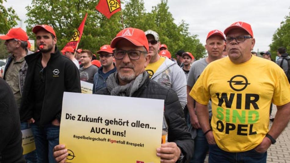 Mitarbeiter verschiedener Opel-Werke tragen bei einer Protestkundgebung der IG Metall vor dem Opel-Werk in Eisenach Plakate, Fahnen und Transparente bei wochenlangen Streitigkeiten. Jetzt wurde eine Einigung bei Opel erzielt.