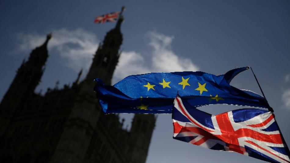 Eine EU-Flagge und eine britische Nationalflagge, der Union Jack, wehen vor dem britischen Parlament im Palace of Westminster, während eine Demonstration gegen den Brexit stattfindet.