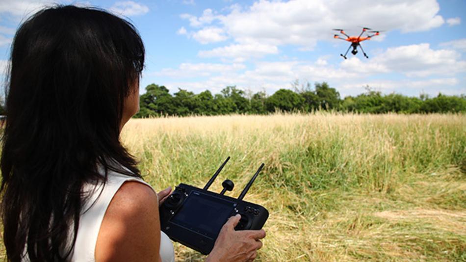 Tierschützerin Dagmar Seidenbecher steuert eine Drohne über ein Feld bei Gera.