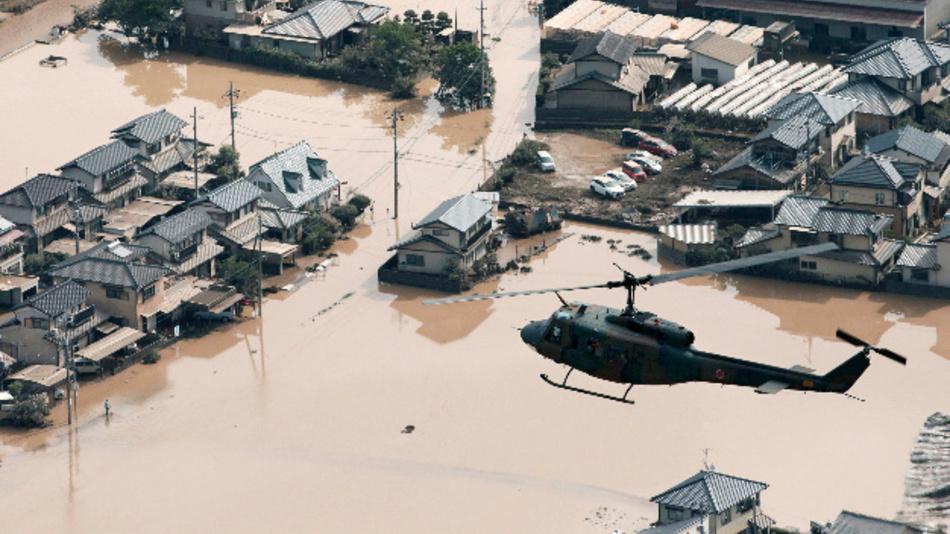 Ein Helikopter fliegt über ein überflutetes Wohngebiet in Kurashiki in der Präfektur Okayama. Bei den Unwettern in Japan sind über 100 Menschen ums Leben gekommen. Heftiger Regen hatte Straßen überflutet und Erdrutsche ausgelöst.