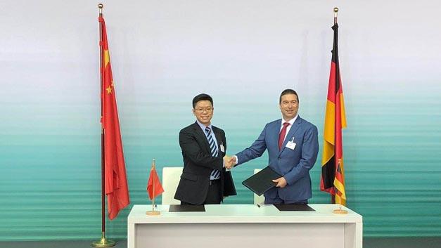 Saad Metz, Executive Vice President von Audi China (rechts) and Veni Shone, President LTE Solution, Huawei besiegeln die gemeinsame Absichtserklärung zur strategischen Kooperation mit dem obligatorischen Handschlag.