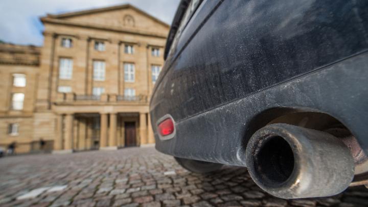 Ein Auto mit dreckiger Stoßstange steht vor dem Gelände des Staatstheaters