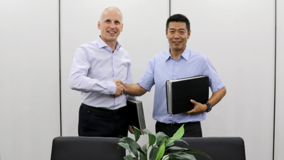 Von links nach rechts: Dietmar Ley (CEO, Basler AG) und Guan Qunli (Vorsitzender Sanbao Xingye (MVLZ) unterzeichnen den Joint-Venture-Vertrag.