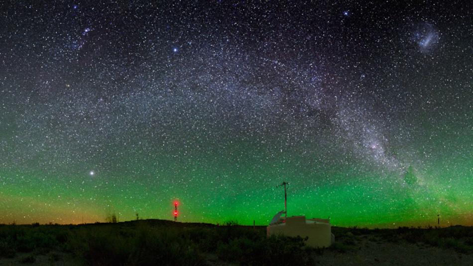Der Nachthimmel mit dem Band der Milchstraße und einer Detektorstation im Vordergrund vor einem der vier Fluoreszenzteleskop-Gebäude, in dem sich sechs Teleskope befinden, die zusammen eine 180-Grad-Sicht erlauben.
