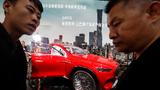 Zwei Chinesen schauen sich die Präsentation von Mercedes-Maybach auf der Automesse in Peking an.