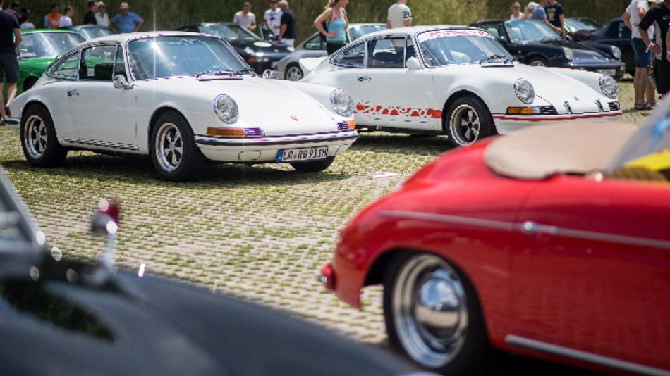Zwei weiße Porsche 911 stehen während dem »Sportscar Together Day« von Porsche nebeneinander. Am 8. Juni 1948 wurde der erste Porsche, der 356 Roadster (rechts im Vordergrund), zugelassen.