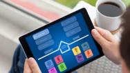 Mann, der ein Tablet mit geöffneter Smart-Home-App hält