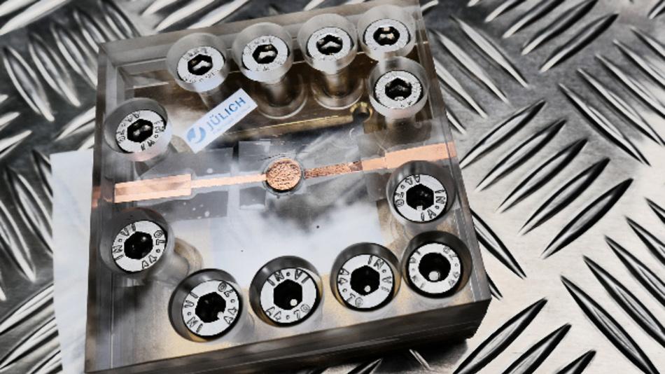 Testaufbau für die Festkörperbatterie: Die Batterie von der Größe einer Knopfzelle befindet sich in der Mitte des Plexiglasgehäuses, welches die dauerhafte Kontaktierung der Batterie sicherstellt. Das patentierte Konzept beruht auf einer günstigen Kombination von Materialien. Alle Komponenten – Anode, Kathode und Elektrolyt – wurden aus verschiedenen Phosphatverbindungen gefertigt, die Laderaten von über 3C (bei einer Kapazität von etwa 50 mAh/g) ermöglichen.