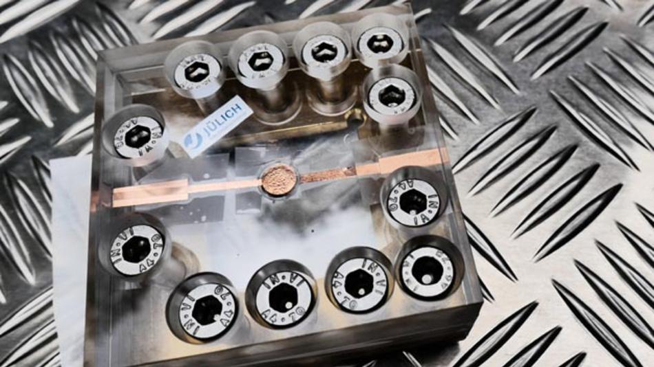 Testaufbau für die neue Festkörperbatterie des FZ Jülich: Die Batterie von der Größe einer Knopfzelle befindet sich in der Mitte des Plexiglasgehäuses, das die dauerhafte Kontaktierung der Batterie sicherstellt.