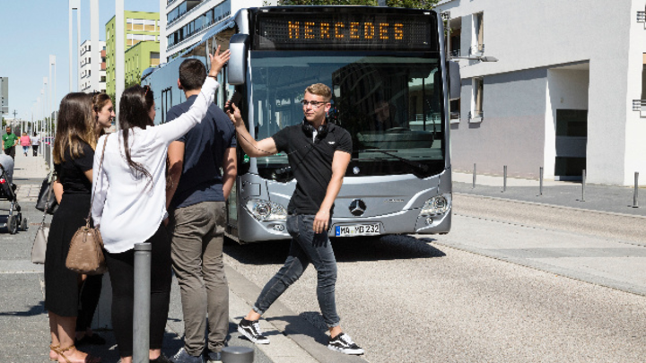 Fußgänger läuft vor herannahenden Stadtbus