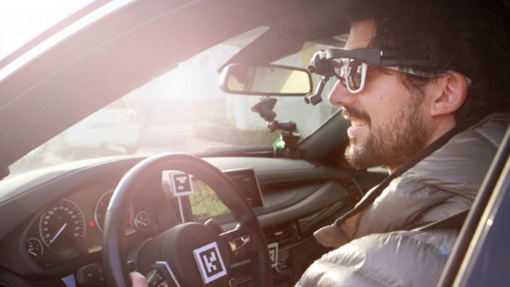 Proband sitzt in einem Versuchsfahrzeug und ist mit unterschiedlichen Sensoren ausgestattet.