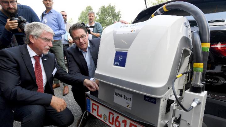 Bundesverkehrsminister Andreas Scheuer (CSU,r) und Ekhard Zinke, KBA-Präsident, hocken vor einer Testfahrt neben einem Auto mit einer Testvorichtung für Abgase.