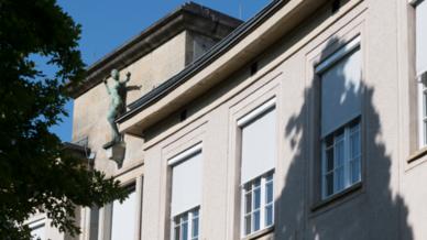 Fassade des Gebäudes von außen mit geschlossenem oder teilgeschlossenem Sonnenschutz.