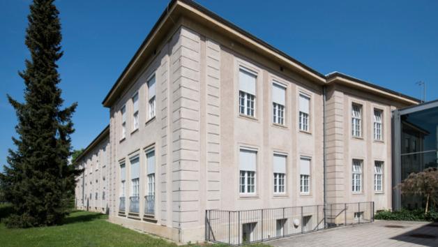 Fassade eines Gebäudes von außen mit geschlossenem oder teilgeschlossenem Sonnenschutz.