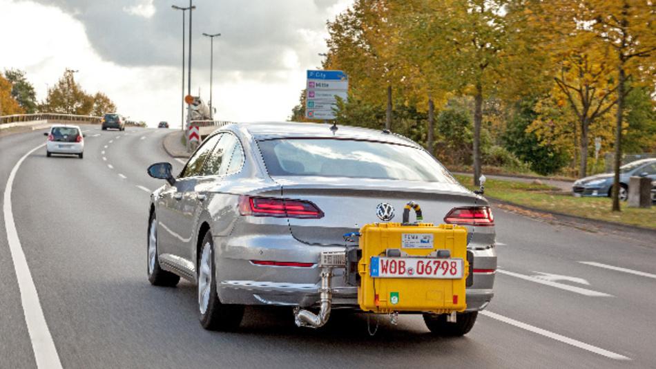Ein Volkswagen Arteon fährt mit einem mobilen Testgerät während einem WLTP-Abgastest auf einer Straße.
