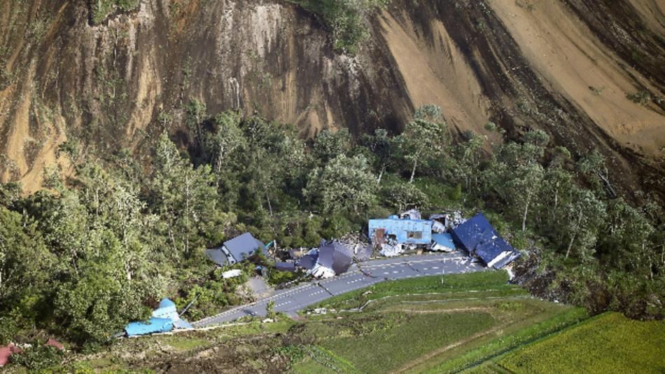 Zerstörte Häuser sind nach einem Erdbeben an der Stelle eines Erdrutsches neben einer Straße zu sehen. Ein Erdbeben der Stärke 6,7 hat auf Japans nördlicher Hauptinsel Hokkaido Schäden verursacht.