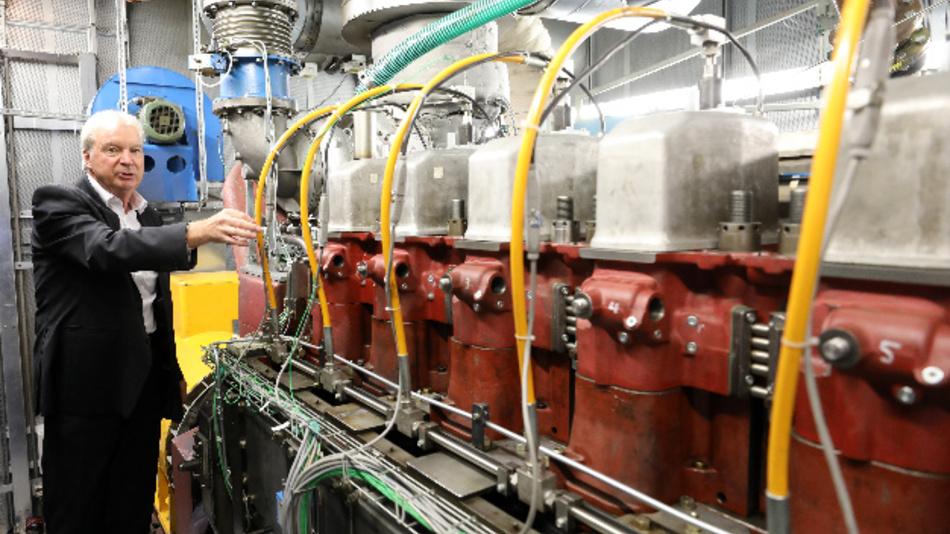 Horst Harndorf, Maschinenbau-Experte und ehemaliger Inhaber des Lehrstuhls für Kolbenmaschinen und Verbrennungsmotoren an der Fakultät für Maschinenbau und Schiffstechnik an der Universität Rostock, steht im Schiffsmotoren-Prüfstand der Universität neben einem Sechs-Zylinder-Hilfsdiesel, an dem die Wissenschaftler neue Einspritzsysteme und Abgasrückführungen testen.