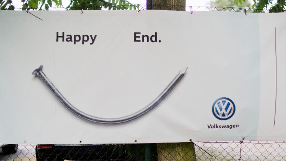 Werbebanner mit Aufschrift »Happy End« und einem verbogenen Nagel hängt am Zaun eines Volkswagen Händlers.